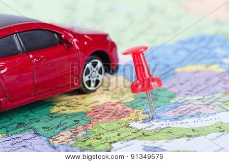 Pushpin And Toy Car On Map