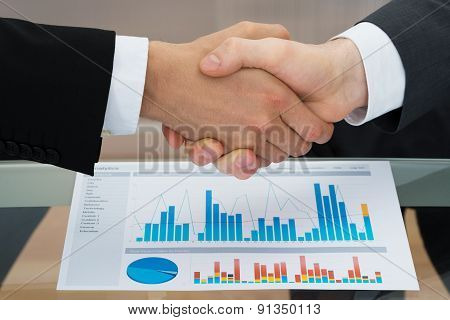 Businesspeople Shaking Hand In Front Of Graph