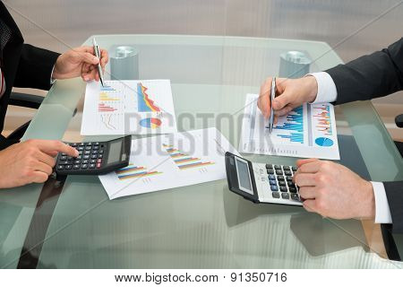 Businessmen Analyzing The Graph On Office Desk