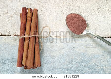Cinnamon sticks tied next a spoon with powdered cinnamon