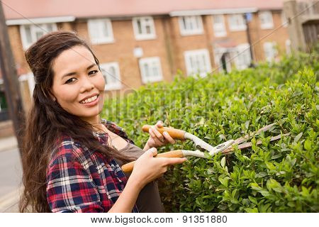 Woman cutting hedge