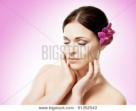 Beautiful face of a young and healthy girl with an orchid flower in her hair over magenta background