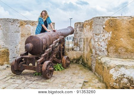 Young tourist posing on old cannon in El Jadida, Morocco