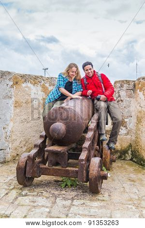 Young couple posing on old cannon in El Jadida, Morocco