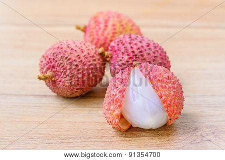 Fresh lychee on a wooden background .