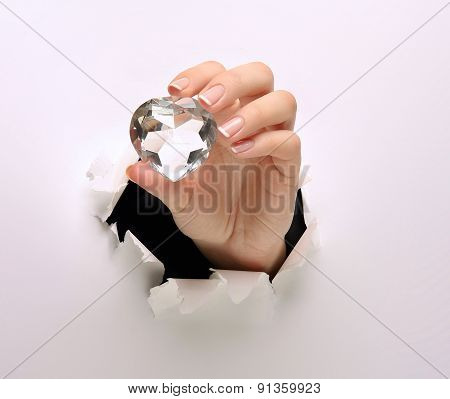 A female hand with a diamond, tearing white paper