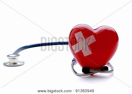 Closeup of a broken heart with a stethoscope, isolated on white