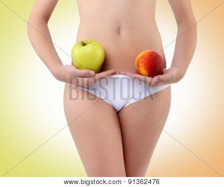 Woman Holding An Apple And Peach With His Hands Near The Belly