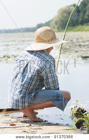 Sitting on wooden bridge shoeless fisherman with fishing rod