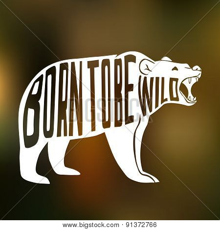Silhouette of wild bear with text inside on blur background.