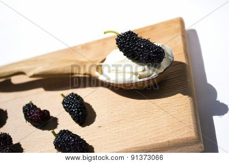 Black Mulberries, Spoon With Sour Cream On Breadboard