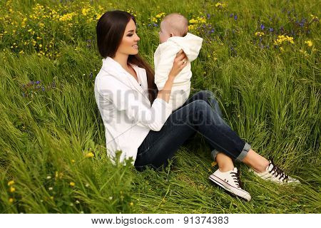 Beautiful Mother Having Fun With Her Little Cute Baby In Summer Garden