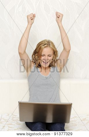 Young woman being happy and putting hands up