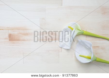 White Calla Lilie On Bright Wooden Background