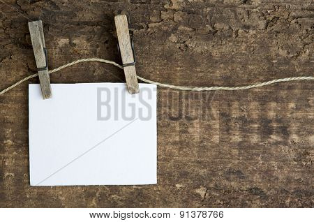 White Paper Hanging On A Clothesline On Rustic Wooden Background