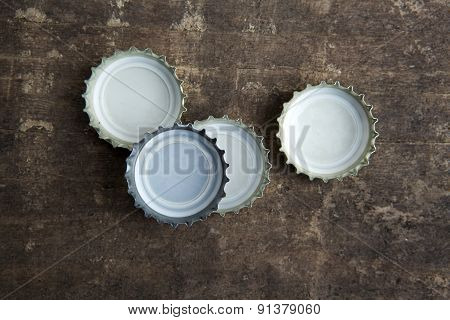 Bottle Caps On Rustic Wooden Background