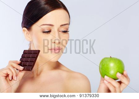 woman with a apple and chocolate in her hand