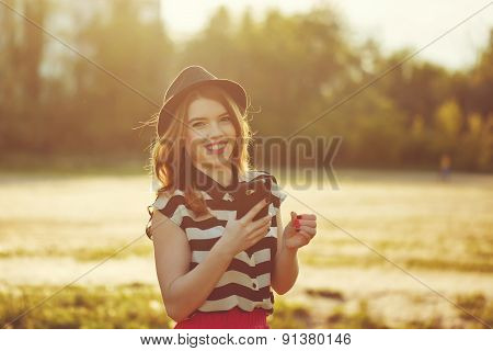 Lovely Girl In A Hat Holding A Cell Phone.