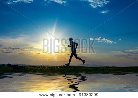 Silhouette Man Running On Meadow Over River, Sunrise -sundown Sky At Background. Runner - Sprinter O