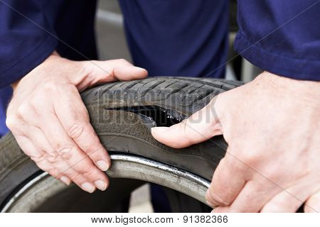 Close Up Of Mechanic Examining Damaged Car Tyre
