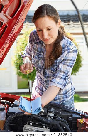 Woman Checking Car Engine Oil Level Under Hood With Dipstick