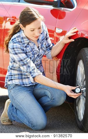 Woman Checking Car Tyre Pressure Using Gauge