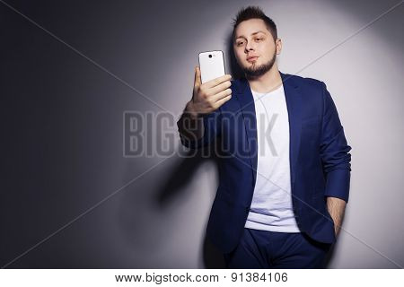Stylish handsome man in blue casual buisness suit working on his phone