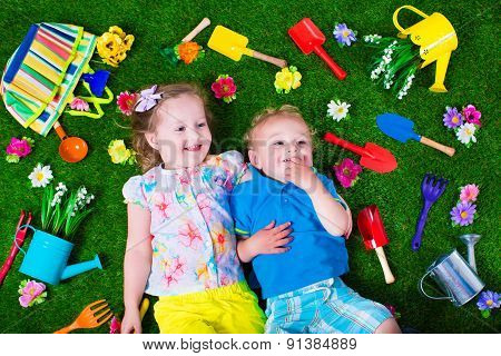 Kids On A Lawn With Garden Tools