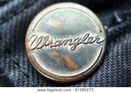 Closeup of Wrangler button on blue jeans