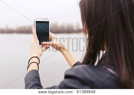 Beautiful Brunette Woman On A Walk In European City Using Her Smartphone Making Photos. Outdoors