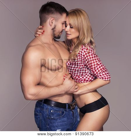 Sexy Fit Muscled Couple In Jeans And Pants And Plaid T-shirt On Neutral Grey Background Hugging