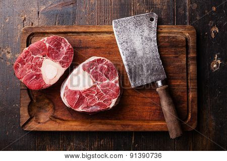 Raw Fresh Cross Cut Veal Shank For Making Osso Buco And Meat Cleaver On Wooden Cutting Board