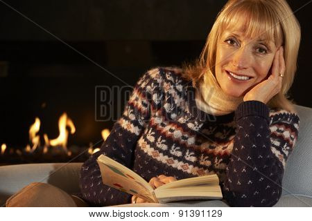 Mature woman reading in front of fire at home