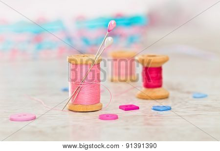 Collection Of Spools  Threads In Pink Colors Arranged On A White Wooden Background