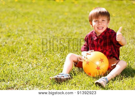 Little boy sitting on grass giving thumbs-up