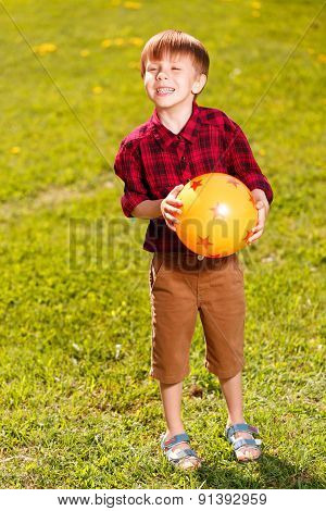 Smiling little boy standing on grass with ball
