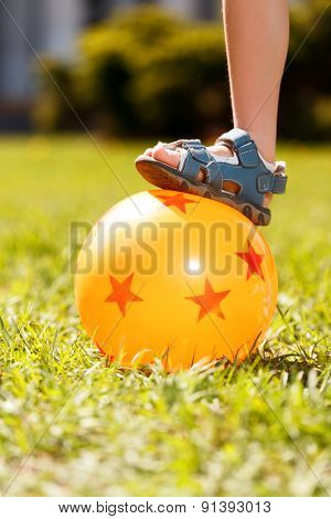Close up of kid putting on ball foot