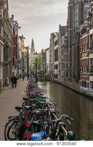 Bicycles Parked Against A Canal In Amsterdam