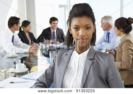 Businesswoman Sitting Around Boardroom Table With Colleagues