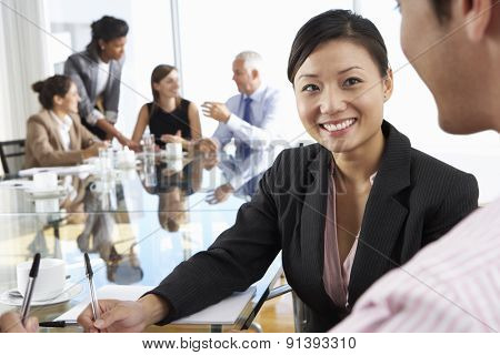 Two People Having Meeting Around Glass Table In Boardroom With Colleagues In Background