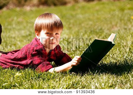 Smiling little kid lying on grass with book