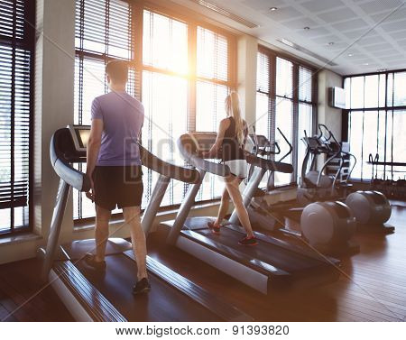 Healthy Man And Woman Running On A Treadmill In A Gym.