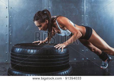 Sportswoman. Fit sporty woman doing push ups on tire strength power training concept crossfit fitnes