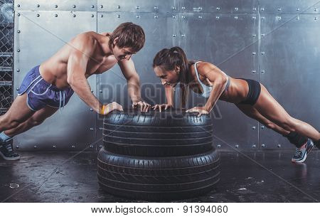 Sportsmen. Fit sporty woman and man doing push ups on tire strength power training concept crossfit