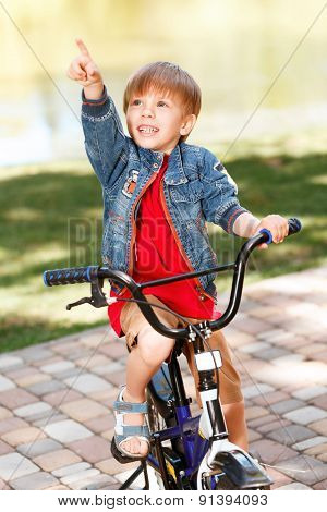Little smiling boy riding bicycle and pointing upwards
