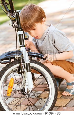 Close up of little boy repairing his bike
