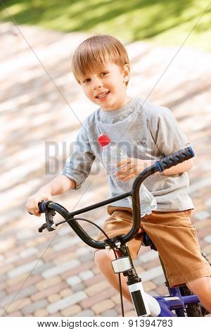 Smiling boy riding bike with bottle of water