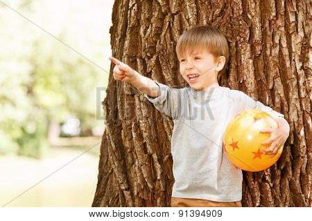 Boy under tree with rubber ball pointing upwards