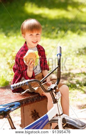 Smiling boy sitting on bench and holding sandwich