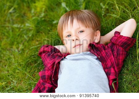 Boy on grass with hands behind his head